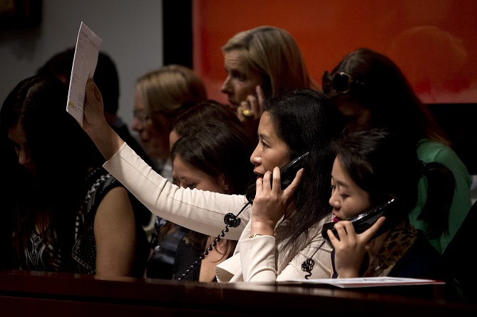 A Christie's employee working the phone holds up her bidders paddle during an auction at Christie's Auction House in the Manhattan borough New York