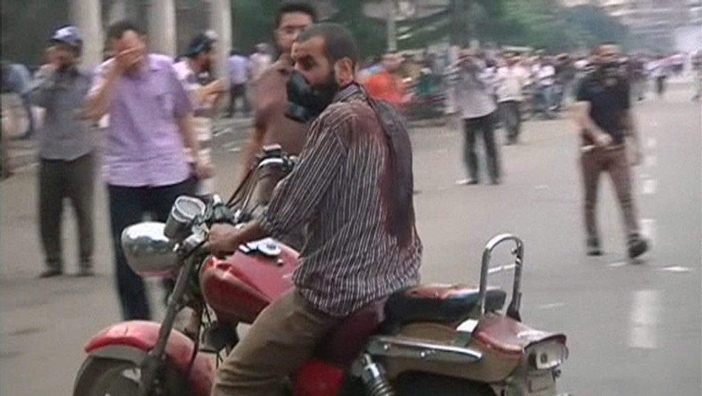 A man wearing a gas mask rides a motorcycle while wearing a blood-drenched shirt as security forces break up the protest camp at al-Nahda square in Cairo