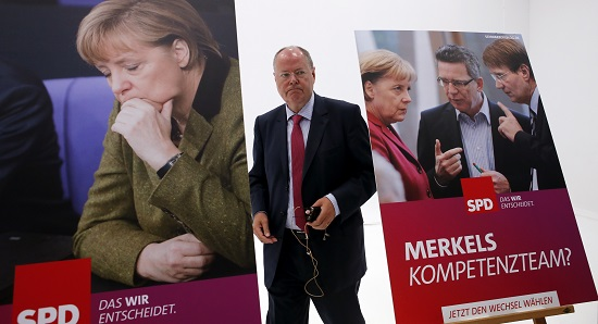 Steinbrueck SPD candidate for German Chancellor in the upcoming general election walks between election campain posters during their official presentation in Berlin