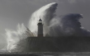 Waves crash against a lighthouse during storms that battered Britain and where a 14-year-old boy was swept away to sea at Newhaven in South East England