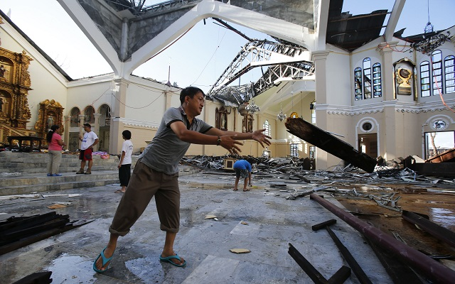 A man throws a broken roof beam onto a pile at the devastated Metropolitan Cathedral of the Archdiocese of Palo, in the aftermath of the Super Typhoon Haiyan, in Palo