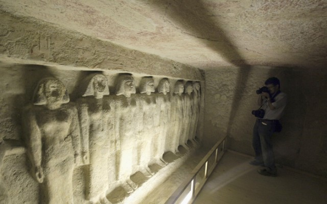 A photographer takes a picture of ancient statues inside the newly opened tomb of Meres Ankh 111 near the pyramids, in Giza