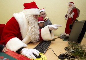 Man dressed as Father Christmas and children look at computer screen at special Christmas post office in village of Himmelpfort