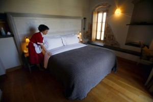 A maid makes a bed in a suite at the Kinsterna Hotel in Agios Stefanos near Monemvasia
