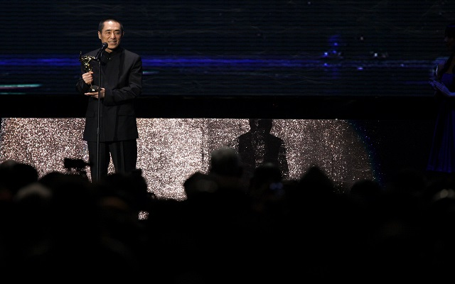 Chinese director Zhang Yimou celebrates with the trophy after winning the Outstanding Contribution to Asian Cinema at the Asian Film Awards in Hong Kong