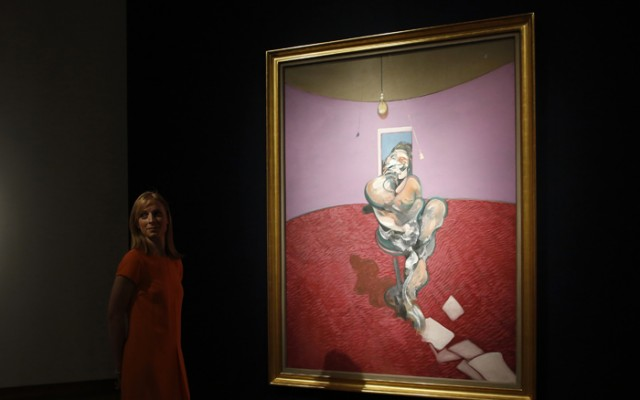 """A gallery assistant poses with """"Portrait of George Dyer Talking"""" by Francis Bacon in 1966 on display at Christie's in London"""