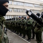 Armed man believed to be a Russian serviceman, stands near members of pro-Russian self defence unit before they take an oath to Crimea government in Simferopol