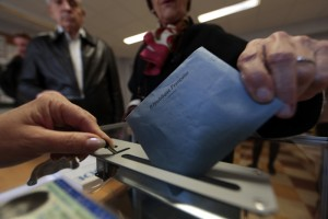A French citizen casts her ballot at a polling station during the first round in the French mayoral elections in Nice