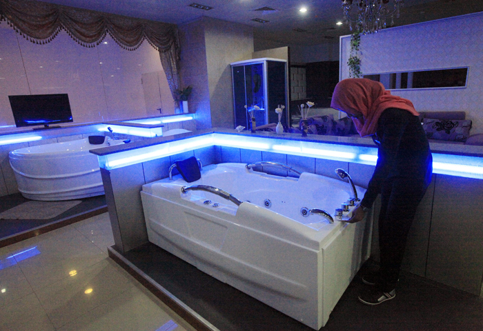 An employee stands near a bathtub for sale at a Chinese Furniture shop at Khartoum's new al-Waha mall