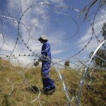 A worker places razor wire around a ventilation shaft used by illegal miners to access an abandoned gold shaft in Benoni