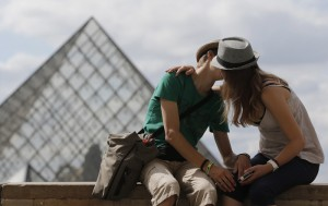 Young tourists kiss as they enjoy a sunny summer afternoon in front of  the Pyramid in the Louvre museum in Paris