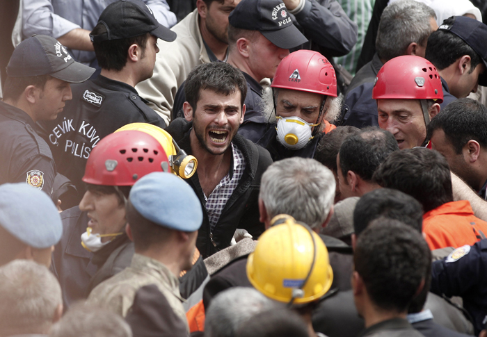 A relative of a miner who was killed or injured in a mine explosion reacts as rescuers work in Soma, a district in Turkey's western province of Manisa