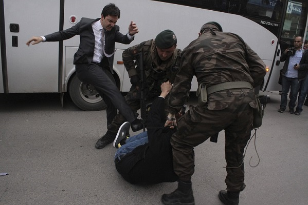 A protester is kicked by Yusuf Yerkel, advisor to Turkey's Prime Minister Tayyip Erdogan, as Special Forces police officers detain him during a protest against Erdogan's visit to Soma