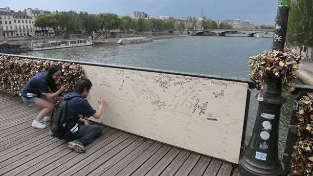 Tourists write on the replacement plank of wood on Pont des Arts