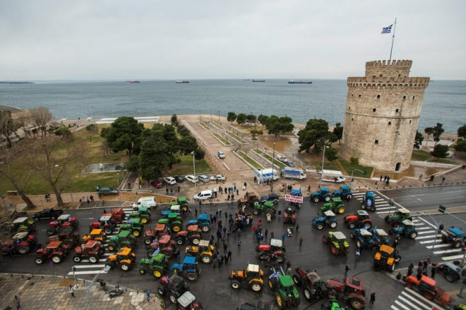 epa05144435 Greek farmers park their tractors to block a road in front of the White Tower, during a protest in Thessaloniki, north Greece, 05 February 2016. Greek farmers protest against the government's proposed tax and pension.  EPA/NIKOS ARVANITIDIS