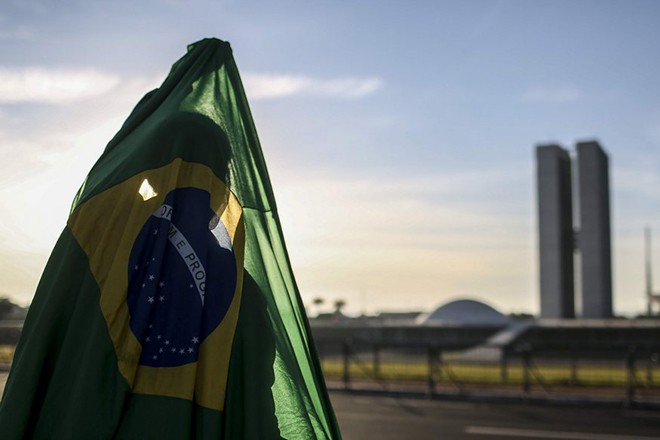 epa05301418 A Brazilian protester holds the Brazilian national flag as he celebrates the impeachment trial against President Dilma Roussef in front of the Lower House in Brasilia, Brazil, 12 May 2016. The Brazilian Senate on early 12 May 2016 voted to suspend Rousseff from power as she stands an impeachment trial. Brazil's lower house of Congress voted on 17 April in favor of impeaching Rousseff for allegedly manipulating budget figures to minimize the deficit. Rousseff denies the allegations, insisting the impeachment process is a coup against her.  EPA/ANTONIO LACERDA