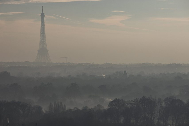 epa05665687 The Eiffel tower is shrouded in haze as the sun comes up, seen from the Mont Valerien in the suburb of Suresnes, near Paris, France, 08 December 2016. Paris is undergoing a third day pollution spike, prompting the city to limit vehicle circulation.  EPA/IAN LANGSDON