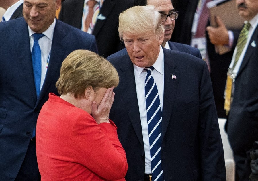 epa06073980 German Chancellor Angela Merkel (L) reacts next to US President Donald J. Trump (R) during the opening session of the G20 summit in Hamburg, Germany, 07 July 2017. The G20 Summit (or G-20 or Group of Twenty) is an international forum for governments from 20 major economies. The summit is taking place in Hamburg 07 to 08 July 2017. EPA/Tore Meek NORWAY OUT