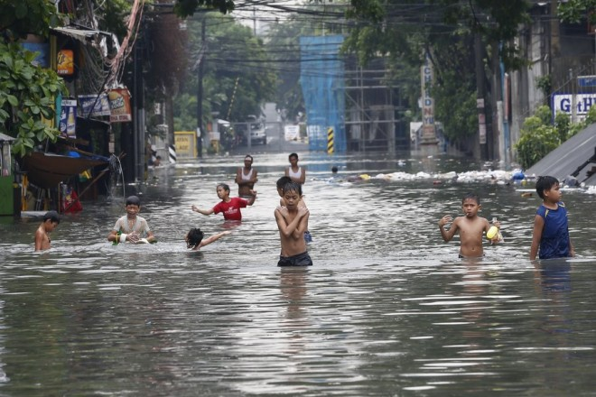 epaselect epa06112061 Filipinos wade in a flooded street in Quezon City, east of Manila, Philippines, 27 July 2017. The center of tropical storm Nesat (local name Gorio) has been estimated at 615 km east of Tuguegarao City, Cagayan province in the northeast area of the Philippines, according to the weather bureau. It is moving with sustained winds of 85 kph near the center and gustiness of up to 105 kph, as it continues to enhance monsoon rains.  EPA/ROLEX DELA PENA