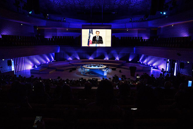 epa06384128 French President Emmanuel Macron's speech is broadcasted during the 'Harnessing Finance: Unlocking the Transformative Role of Finance for Climate' panel at the Seine Musicale during the One Planet Summit on the Ile Sequin near Paris, France, 12 December 2017.  EPA/ETIENNE LAURENT