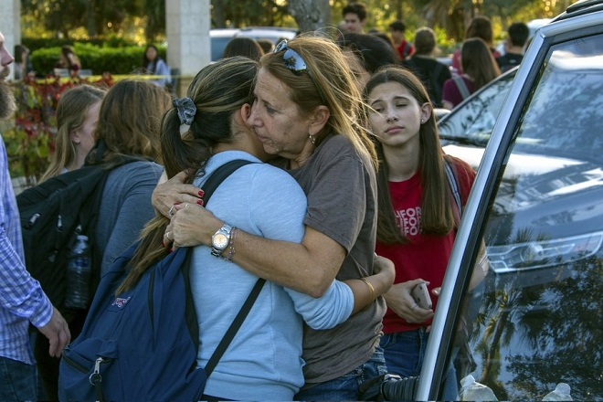 epa06525832 Students are reunited with parents and family after a shooting at Marjory Stoneman Douglas High School in Parkland, Florida, USA, 14 February 2018. Multiple fatalities have been reported and several more injured at a high school northwest of Miami. According to law enforcement the suspect is in custody. Some media are reporting the suspect as  former student, Nicolas Cruz.  EPA/GIORGIO VIERA