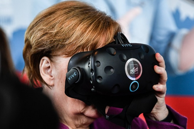 epa06691375 German Chancellor Angela Merkel uses  Virtual Reality System during international 'Girl's Day' at the chancellery in Berlin, Germany, 25 April 2018.  EPA/FILIP SINGER