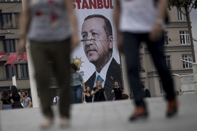 epa06841766 People walk in front of the poster of Turkish President Recep Tayyip Erdogan which reads, 'Thank you Istanbul' at Taksim Square in Istanbul, Turkey, 26 June 2018.  Turkish Electoral Commission on 26 June announced Recep Tayyip Erdogan has won the presidential elections. In the parliamentary elections, which were held at the same time as the presidential elections, although the Justice and Development Party (AKP) won with 42.5 percent of the votes, it lost the absolute majority which the party had secured in the parliament since 2002.  EPA/SEDAT SUNA