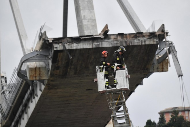 epa06949824 Rescuers at work after a highway bridge collapsed in Genoa, Italy, 14 August 2018. At least 22 people are believed to have died as a large section of the Morandi viaduct upon which the A10 motorway runs collapsed in Genoa. Both sides of the highway fell. Around 10 vehicles are involved in the collapse, rescue sources said. The viaduct gave way amid torrential rain.  EPA/LUCA ZENNARO