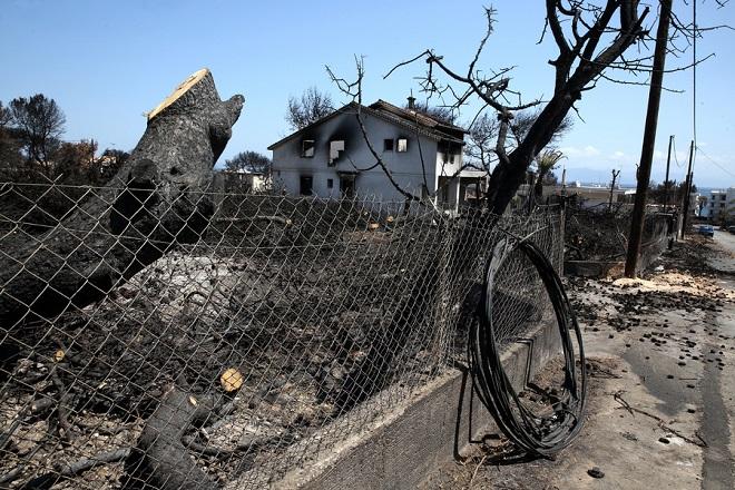 Καμένοι κορμοί δέντρων σε κτήμα με καμένο σπίτι στο Μάτι Αττικής, Κυριακή 19 Αυγούστου 2018, μετά την πυρκαγιά που ξέσπασε στην περιοχή στις 23 Ιουλίου αφήνοντας πίσω της 94 νεκρούς και τεράστιες καταστροφές σε οικείες και περιουσίες. ΑΠΕ-ΜΠΕ/ΑΠΕ-ΜΠΕ/ΣΥΜΕΛΑ ΠΑΝΤΖΑΡΤΖΗ