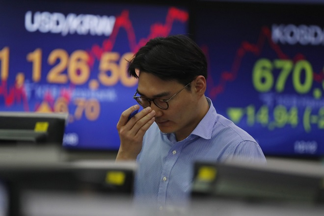 epa07220937 A South Korean dealer works in front of monitors at the KEB Hana Bank in Seoul, South Korea, 10 December 2018. The benchmark South Korea Composite Stock Price Index (KOSPI) plummeted 21.97 points, or minus 1.06 percent to close at 2,053.79 points on what is believed be the concerns over trade disputes between the United States and China.  EPA/JEON HEON-KYUN