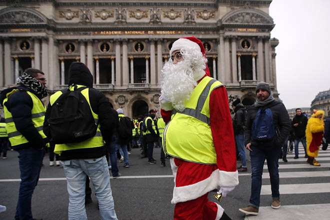 epa07232362 A Yellow Vest protestor wearing a Santa Claus outfit attends a demonstration in front of the Opera in Paris, France, 15 December 2018. The so-called 'gilets jaunes' (yellow vests) is a protest movement, which reportedly has no political affiliation, that continues protests across the nation over high fuel prices.  EPA/IAN LANGSDON