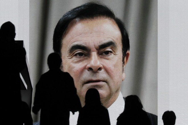 epa07274584 (FILE) - Pedestrians watch a large-scale screen displaying a news program reporting on former Nissan Motor Co Ltd chairman Carlos Ghosn attending a court hearing at Tokyo district court, in Tokyo, Japan, 08 January 2019 (reissued 11 January 2019). Prosecutors in Japan have charged former Nissan chairman Carlos Ghosn with two new charges of financial crime. Ghosn, who has been in prison since November 2018, has been charged with serious breach of trust and undervaluation of his income.  EPA/KIMIMASA MAYAMA