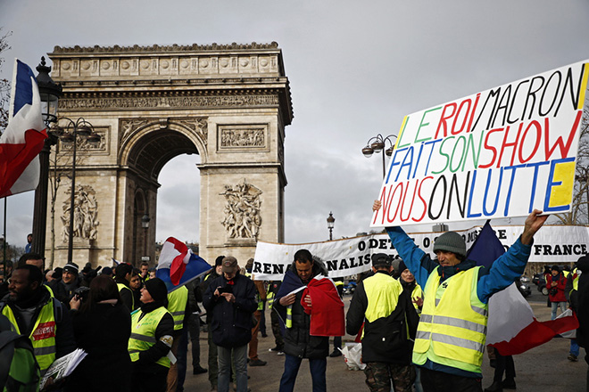epa07321028 A protesters from the 'Gilets Jaunes' (Yellow Vests) movement holds a poster reading 'Macron is doing his show, we are fighting' during the 'Act XI' demonstration (the 11th consecutive national protest on a Saturday) in Paris, France, 26 January 2019. The so-called 'gilets jaunes' (yellow vests) is a grassroots protest movement with supporters from a wide span of the political spectrum, that originally started with protest across the nation in late 2018 against high fuel prices. The movement in the meantime also protests the French government's tax reforms, the increasing costs of living and some even call for the resignation of French President Emmanuel Macron.  EPA/CHRISTOPHE PETIT TESSON