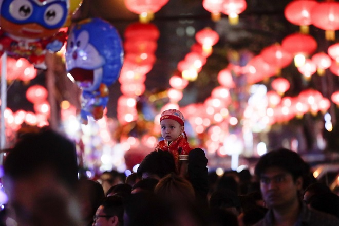epa07343406 A child sits on a man's shoulder as people take part the celebration on the eve of Chinese Lunar New Year in Yangon, Myanmar, 04 February 2019.The Chinese New Year, the Year of the Pig, begins on 05 February 2019 and ends on 24 January 2020.  EPA/LYNN BO BO