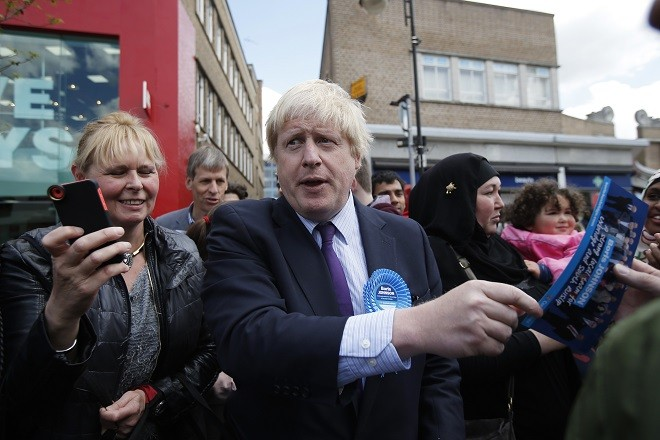 London Mayor Boris Johnson hands out leaflets during campaigning for the local parliamentary seat in Uxbridge, west London, Britain