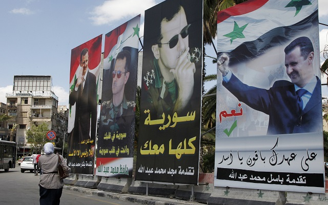 A woman walks past election posters of Syria's President Bashar al-Assad along a street in Damascus