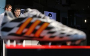 Adidas CEO Hainer is pictured behind a soccer shoe during a news conference in Herzogenaurach
