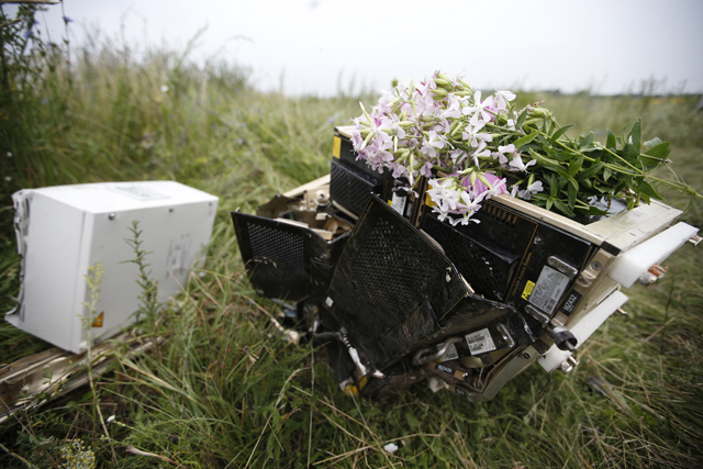 Flowers lie on debris from a Malaysian Airlines Boeing 777 plane which was downed on Thursday near the village of Rozsypne
