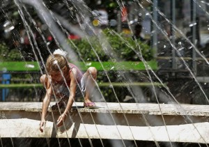A child cools off at a public fountain in downtown Bucharest