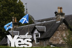 Scottish flags fly above a sign in support of the Yes campaign outside a house in Pitlochry , Scotland
