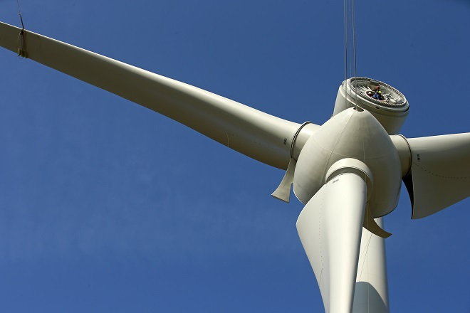 A worker installed in the nacelle looks at the lifting of the hub with rotor blades of an E-70 wind turbine manufactured by German company Enercon for La Compagnie du Vent during its installation at a wind farm in Meneslies, Picardie region