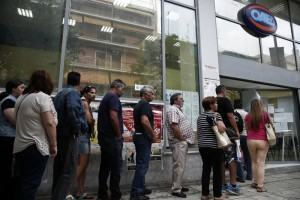 People wait outside a Greek Manpower Employment Organisation (OAED) office in a suburb of Athens