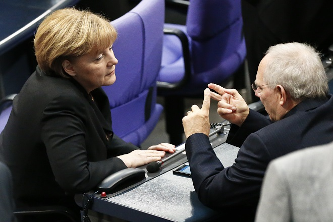 German Chancellor Merkel speaks to designated Finance Minister Schaeuble during a meeting in the Bundestag, the lower house of parliament, in Berlin