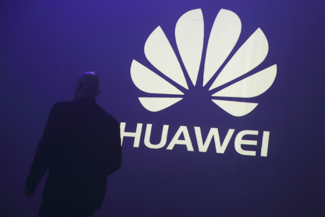 A man walks past a logo during the presentation the Huawei's new smartphone, the Ascend P7, launched by China's Huawei Technologies in Paris