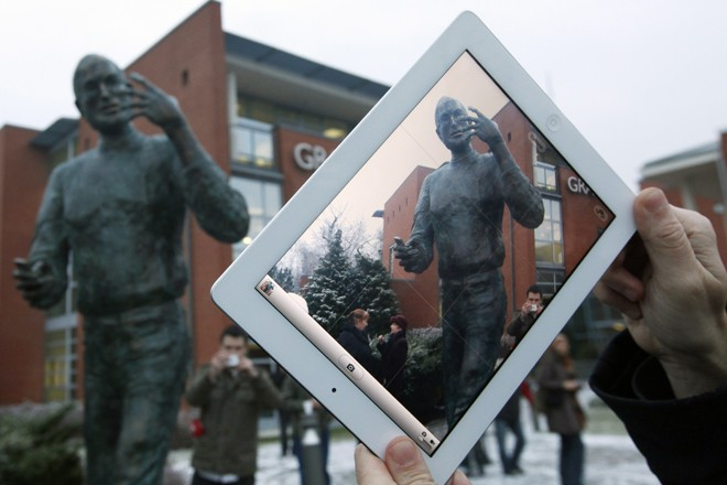 A man takes pictures with his iPad during the unveiling ceremony of a statue of Steve Jobs at a private business park in Budapest