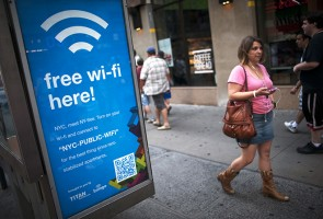 A woman walks past a WiFi-enabled phone booth in New York