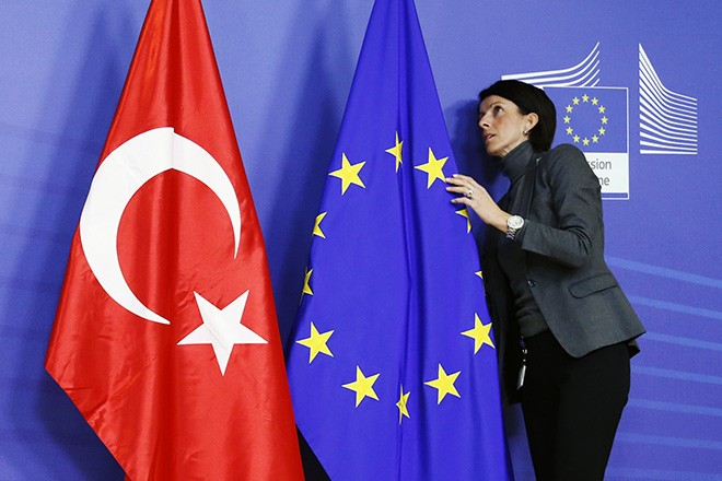 A staff adjusts European Union and Turkish flags ahead of the arrival of Turkey's PM Erdogan at the EU Commission headquarters in Brussels