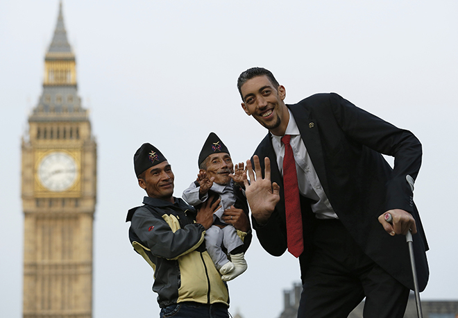 The world's shortest man Chandra Bahadur Dangi is held by nephew Dolakh Dangi as they pose with the tallest living man Sultan Kosen to mark the Guinness World Records Day in London