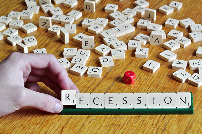 A man makes the word recession from letters of a scrabble game in this illustration picture taken in Ljubljana