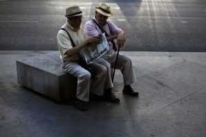 Two elderly men read the paper together in central Madrid